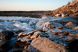 """Il complesso produttivo delle saline è situato nel comune italiano di Margherita di Savoia (nome dato dagli abitanti in onore alla regina d'Italia che molto si adoperò nei confronti dei salinieri) nella provincia di Barletta-Andria-Trani in Puglia. Sono le più grandi d'Europa e le seconde nel mondo, in grado di produrre circa la metà del sale marino nazionale (500.000 di tonnellate annue).All'interno dei suoi bacini si sono insediate popolazioni di uccelli migratori e non, divenuti stanziali quali il fenicottero rosa, airone cenerino, garzetta, avocetta, cavaliere d'Italia, chiurlo, chiurlotello, fischione, volpoca..Un piccola """"cascata"""" tra sassi e incrostazioni di sale. Si tratta dell'acqua che viene fatta defluire da un bacino all'altro attraverso una chiusa (non inquadrata)."""