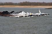 Nederland, Millingen, 1-3-2018 Een binnenvaartschip, een duwbakcombinatie, heeft een met ijs en ijspegels bedekte boeg door het bevriezen van het buiswater . Door de vorst verandert de kleur van de eerste kolenhoop van zwart naar wit. Foto: Flip Franssen
