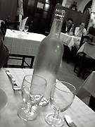 restaurant in europe.interior close up of water bottle wine galsses on table with tables in background,black and white,verticle