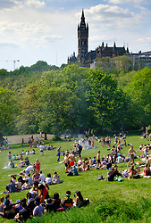 Hot weather and people in Glasgow Kelvingrove Park with Glasgow University to rear in Glasgow West End, Scotland, UK