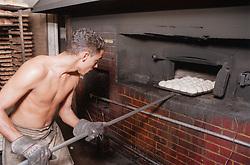 Baker putting bread rolls into oven in bakery; Havana; Cuba,