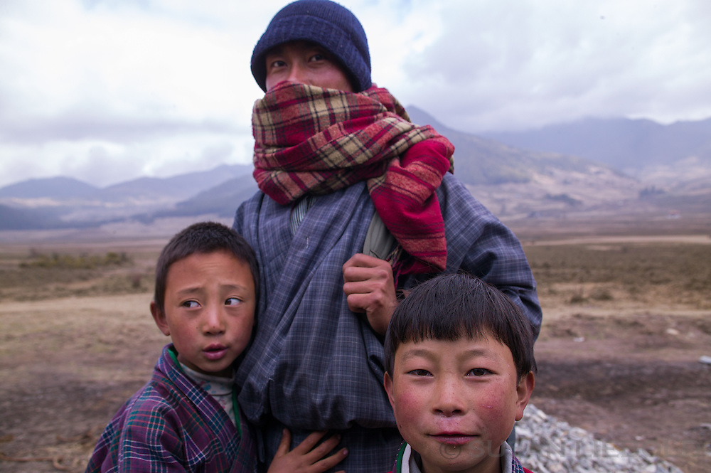 A man with two boys in the Phobjica Valley in Bhutan.