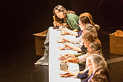 Brooklyn, NY - 11 December 2019. A performance of In Many Hands in BAM's Fishman Space, by Kate McIntosh in collaboration with Arantxa Martinez and Josh Rutter; sound design by John Avery; lighting design by Joëlle Reyms. The piece involves participants sitting at 3 long, narrow tables, with facilitators at each end, and either passing along objects—here a block of granite—or repeating hand movements in the manner set by a facilitator.