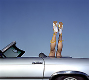 Legs of a woman coming out of convertible