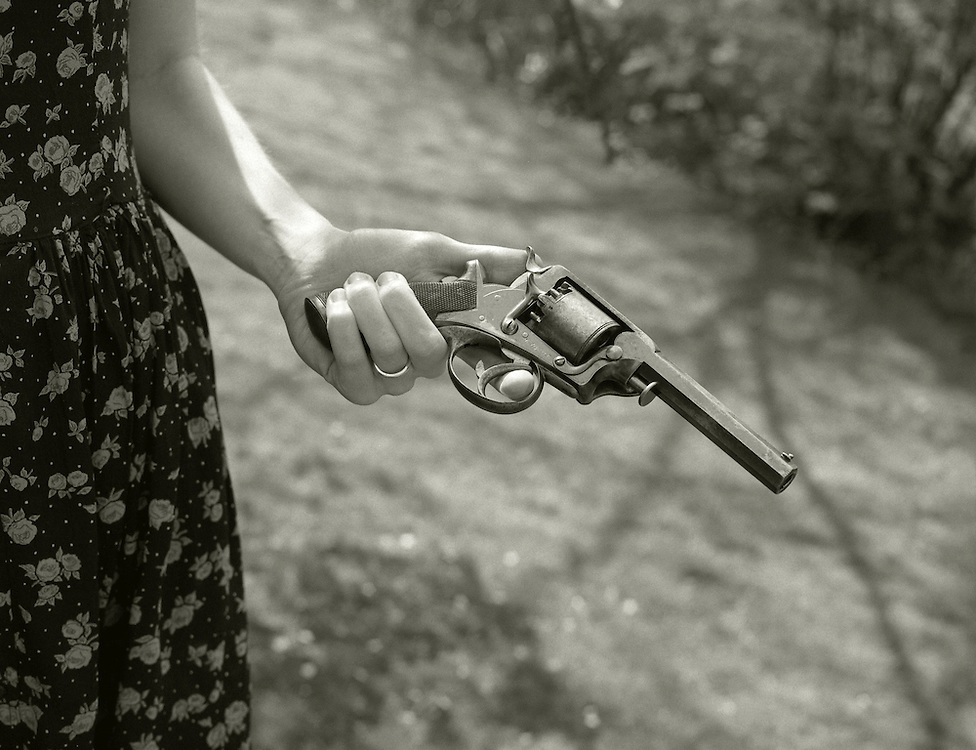 A woman in a print dress holds a revolver.<br /> [This photograph is currently licensed through GalleryStock - please contact the photographer for details]