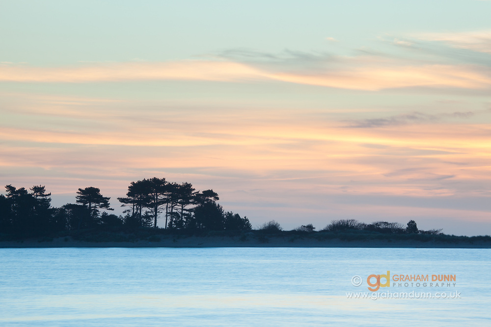 Dawn skies silhouette the distinctive trees on East Hills. Captured from Wells beach, north Norfolk, East Anglia.
