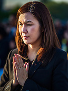 20 JANUARY 2017 - BANGKOK, THAILAND: People pray during a merit making ceremony on the plaza in front of Bangkok's City Hall. Hundreds of municipal workers and civil servants made merit by praying and presenting alms to 89 Buddhist monks Friday to mark 100 days of mourning since the death of revered Bhumibol Adulyadej, the Late King of Thailand. The significance of 89 monks is that the King, who died on October 13, 2016, was a few weeks short of his 89th birthday.        PHOTO BY JACK KURTZ