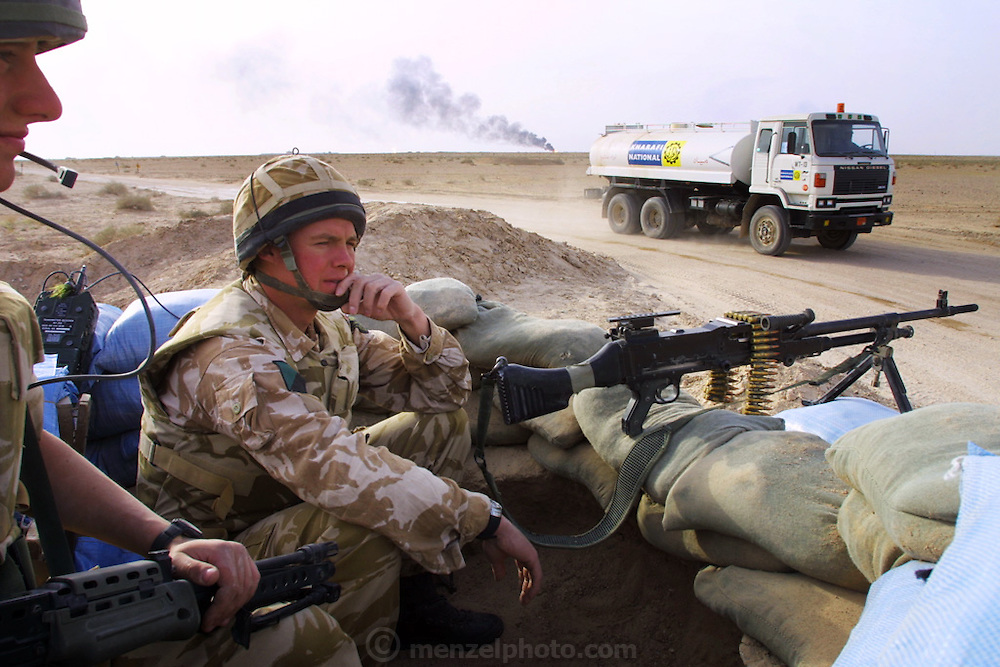 Paul Ross Muir and Philip Murray of the Royal Irish Regiment man a checkpoint that is part of the British effort to secure areas around burning oil wells in Iraq's Rumaila Oil Field, in southern Iraq. The wells were set on fire with explosives placed by retreating Iraqi troops when the US and UK invasion began. Seven or eight wells were set ablaze and at least one other was detonated but did not ignite. The Rumaila field is one of Iraq's biggest oil fields with five billion barrels in reserve. Many of the wells are 10,000 feet deep and produce huge volumes of oil and gas under tremendous pressure, which makes capping them very difficult and dangerous. Rumaila is also spelled Rumeilah.