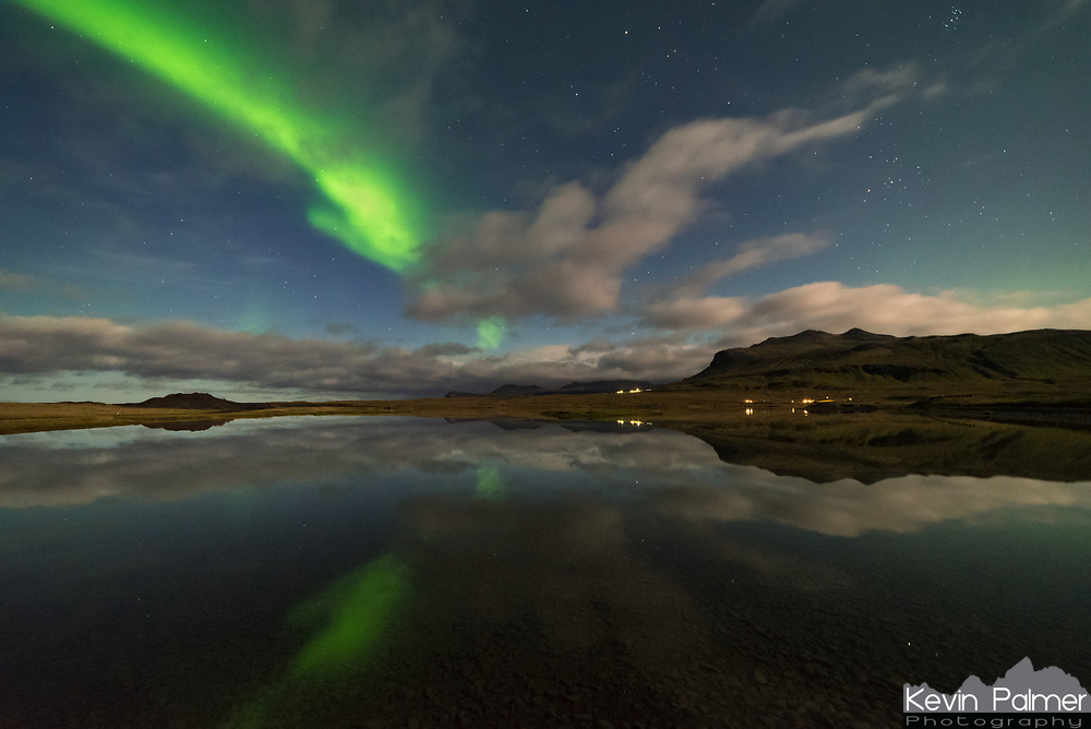 After waiting hours for thick clouds to clear over Grundarfjörður, I gave up and headed back to my campsite. But to my surprise the clouds parted briefly as I got close to Olafsvik. I stopped at this perfectly calm lagoon, which was lit up by the moonlight. The aurora wasn't as active as before, but it was still visible.