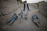 An Afghan villager walks among US  soldiers from L Trp 4/25CR, who pull security  at a check point in Kandahar City, Afghanistan, Thursday,   Oct 21, 2010. (AP Photo/Rodrigo Abd)