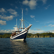Sailing boat in the evening sun in front of West-Papua main land.