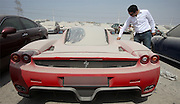 Most expensive police sale in history: Limited edition £1million Ferrari abandoned to the Dubai dust after debt-ridden British owner flees country to be auctioned off <br /> <br /> A £1million limited edition Ferrari is to be auctioned in what is thought to be the most expensive police sale in history, it was revealed today.<br /> The exclusive Enzo, one of only 399 in the world, was impounded by officers last year after it was abandoned in a car park and covered in dust in Dubai.<br /> It is to go under the hammer on Wednesday among 23 luxury vehicles in a special supercar police sale, local officers confirmed today.<br /> The red motor - owned by a Brit - is one of the top 10 fastest ever road cars ever produced.<br /> It is thought the owner was being chased for unpaid traffic fines after abandoning the supercar 20 months ago.<br /> Lots of expats abandon their expensive cars because in Dubai being in debt is a crime.<br /> <br /> Many then skip the country to avoid jail and until recently they were automatically put on the Interpol wanted list by the rich Arab state's authorities.<br /> There is no suggestion that the British owner - who has not been named - was involved in serious criminality.<br /> The supercar has an eye-watering 5998c aluminium V12 engine capable of 660bhp and a top speed of 217mph.<br /> <br /> It can reach 0-60mph in just 3.4 seconds and Enzos, first built in 2002, are so rare that every time one crashes the others increase in value.<br /> The Enzo is the prize of the auction, but it will be joined in the sale by three other Ferraris, as well as seven top-of-the-range Porsches, Corvettes, Mercedes, BMWs, Infinitis, Range Rovers and Dodges.<br /> But it was inexplicably left to gather dust in a compound in the Gulf nation and was seized in June 2011.<br /> <br /> Now it will go up in front of bidders in what looks set to be the most lucrative police auction of lost and found goods in history.<br /> A total of 129 cars will be auctioned star