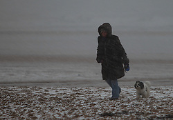 Licensed to London News Pictures. 05/12/2012. Tynemouth, UK, A woman and her dog brave a snowstorm on Longsands beach, Tynemouth, Tyne & Wear. Photo credit: Adrian Don/LNP
