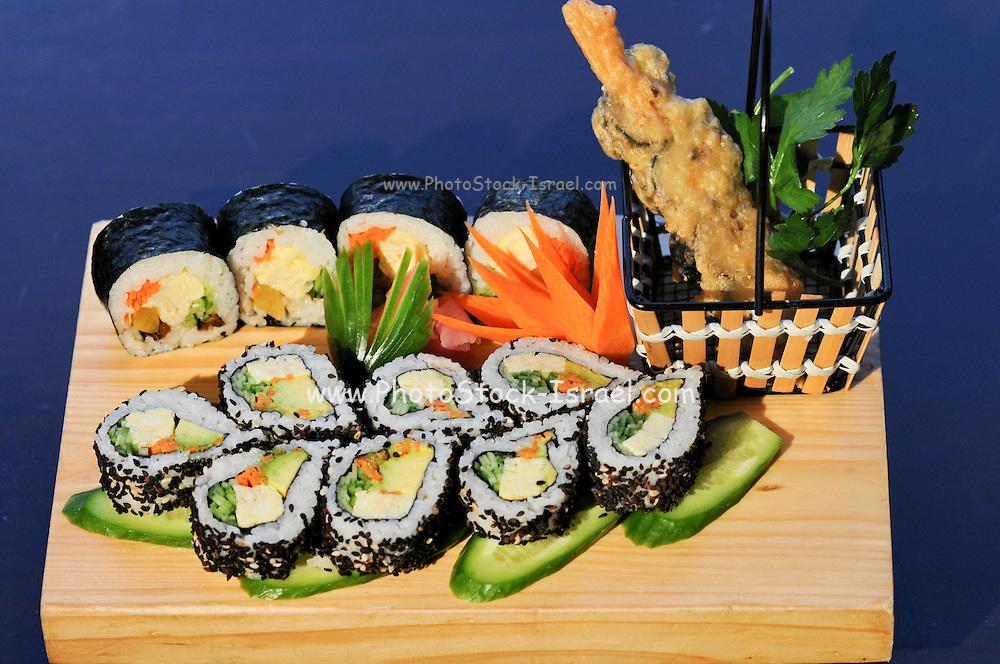 Assortment of Sushi on a wooden platter including: Sushi Maki, futo maki, Insideout and tempura