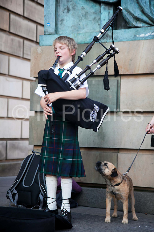 A small boy plays the bag pipe in te Royal Mile during the Edinburgh Festival. His dog sings along to the tune.
