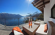 Terrace with comfortable divan and lake view in a luxury house