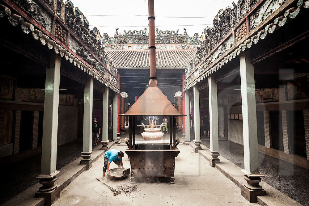 A Vietnamese man empties ashes from a censer in a pagoda of Cholon, Ho Chi Minh City, Vietnam, Southeast Asia