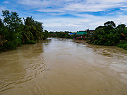 09 AUGUST 2018 - BAN LAEM, PHETCHABURI, THAILAND: The Phetchaburi River flowing through Ban Laem. The river is about a meter below flood stage. The Phetchaburi River flows from Kaeng Krachan Dam to the Gulf of Siam through several towns including Ban Lat, Phetchaburi (the capital of Phetchaburi province) and Ban Laem. Government officials have warned residents of those towns that their towns will flood because the reservoir behind the dam is approaching capacity. Ban Lat and Phetchaburi could be flooded for several weeks. Residents of Ban Laem have been warned that their community could be inundated for over a month. Dams in Kanchanaburi province, west of Phetchaburi, are also approaching capacity and flooding is also expected in that area.   PHOTO BY JACK KURTZ