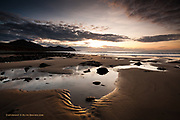 Sunset over Aberdesach beach at low tide, on the Northern edge of the Llyn Peninsula in North Wales, revealing rock pools in the wide beach. The mountains of Gyrn Goch, Yr Eifl and Garn For are in the background.