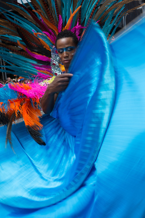A man in a large feathered headdress waves his turquoise cape.