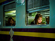 31 MAY 2017 - CHACHOENGSAO, THAILAND: A passenger catches up on news on her smart phone while she waits for the 5.45AM train to leave the train station in Chachoengsao, a provincial town about 50 miles and about an hour by train from Bangkok. The train from Chachoengsao to Bangkok takes a little over an hour but traffic on the roads is so bad that the same drive can take two to three hours. Thousands of Thais live outside of Bangkok and commute into the city for work on trains, busses and boats.       PHOTO BY JACK KURTZ