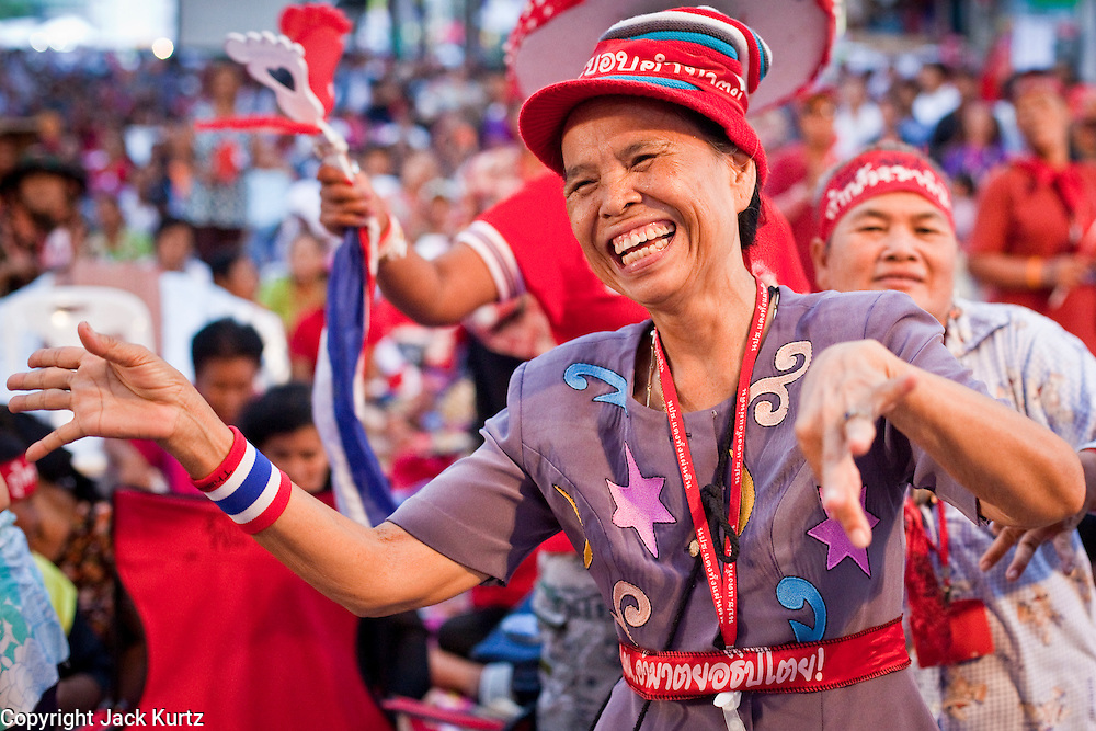 """06 MAY 2010 - BANGKOK, THAILAND:  Red Shirt women cheer and dance in Ratchaprasong intersection Thursday night. Red Shirt protestors in Ratchaprasong intersection, Thursday May 6, more than one month after the Reds occupied the intersection. Members of the United Front of Democracy Against Dictatorship (UDD), also known as the """"Red Shirts"""" and their supporters moved their anti government protests into central Bangkok Apr. 4 when they occupied Ratchaprasong intersection, the site of Bangkok's fanciest shopping malls and several 5 star hotels. The Red Shirts are demanding the resignation of current Thai Prime Minister Abhisit Vejjajiva and his government. The protest is a continuation of protests the Red Shirts have been holding across Thailand. They support former Prime Minister Thaksin Shinawatra, who was deposed in a coup in 2006 and went into exile rather than go to prison after being convicted on corruption charges. Thaksin is still enormously popular in rural Thailand. This move, away from their traditional protest site in the old part of Bangkok, has gridlocked the center of the city and closed hundreds of stores and restaurants and several religious shrines. On Thursday night the Red Shirt leaders said there has been a """"glitch"""" in the ongoing negotiations to end the standoff. Their opponents, the """"Yellow Shirts"""" who previously supported the incumbent Prime Minister have rejected his peace plan and called for the PM to resign.  PHOTO BY JACK KURTZ"""