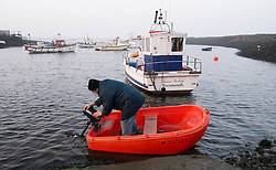 © Licensed to London News Pictures. 13/03/2014<br /> <br /> South Gare, Teesside, England, UK<br /> <br /> A fisherman starts an outboard motor as he makes his way to his larger fishing boat moored further from shore in a small fishing community known as Paddy's Hole at South Gare on the mouth of the River Tees on Teesside.<br /> <br /> Photo credit : Ian Forsyth/LNP