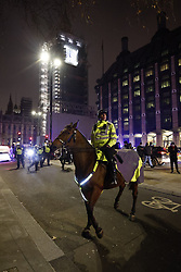 © Licensed to London News Pictures. 31/12/2020. London, UK. Mounted police try to disperse crowds gathering on New Year's Eve near Parliament in central London. Photo credit: Peter Macdiarmid/LNP