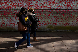"© Licensed to London News Pictures. 08/04/2021. London, UK. Amanda Herring (left) carries a photograph of her brother Mark Herring, who died of COVID-19 aged 54, as she ""walks the wall"" to mark the completion of the approximately 150,000 hearts painted onto the National Covid Memorial Wall on the Thames Embankment opposite the Houses of Parliament. Members of the public are invited to walk the length of the memorial, and campaigners are asking Prime Minister Boris Johnson to make the memorial permanent. Photo credit: Rob Pinney/LNP"