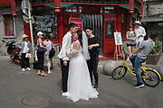 Brides and couples to be get their photographs taken in the streets of Beijing before their weddings. China
