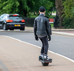 © Licensed to London News Pictures. 13/05/2020. London, UK. A member of the public uses an electric skateboard in Hyde Park as the Government relaxes the law on lockdown today to let people spend more time outside to enjoy the fresh air, picnics, sunbathing and meet other people while following social distancing guidelines. Photo credit: Alex Lentati/LNP