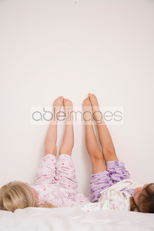 Two girls lying on bed with legs up white wall