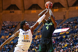 Jan 21, 2019; Morgantown, WV, USA; Baylor Bears guard Mario Kegler (4) shoots a three pointer while defended by West Virginia Mountaineers forward Andrew Gordon (12) during the first half at WVU Coliseum. Mandatory Credit: Ben Queen-USA TODAY Sports