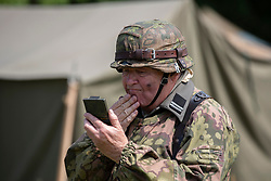 © Licensed to London News Pictures. 27/04/2018. Denmead, UK. A participant prepares to himself before a skirmish as he takes part in the Overlord Military Spectacular, a gathering of military re-enactors. The event, 1st held in 1977, is organised by The Solent Overlord Military Collectors Club and features some 200 military vehicles and 500 re-enactors dressed in authentic uniforms and equipment from the era.   Photo credit: Julian Herbert/LNP