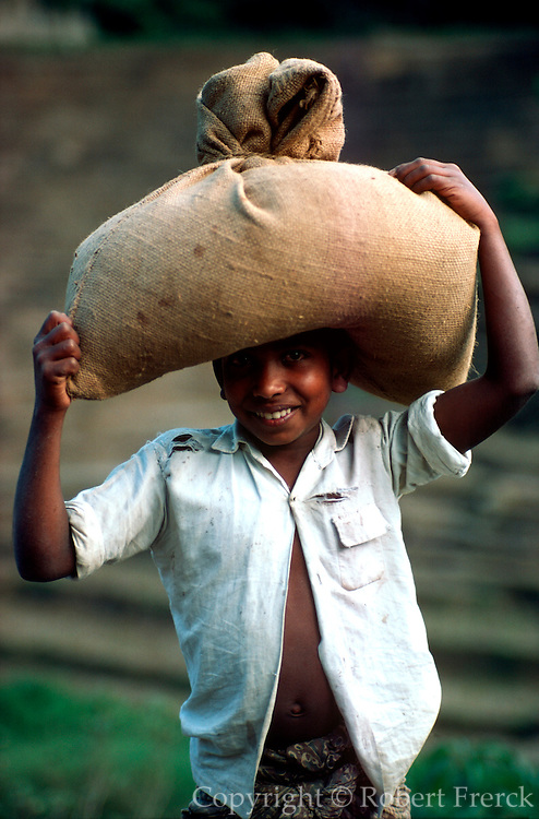 INDIA, PORTRAITS Portrait of boy in Southern India carrying sack of coffee beans