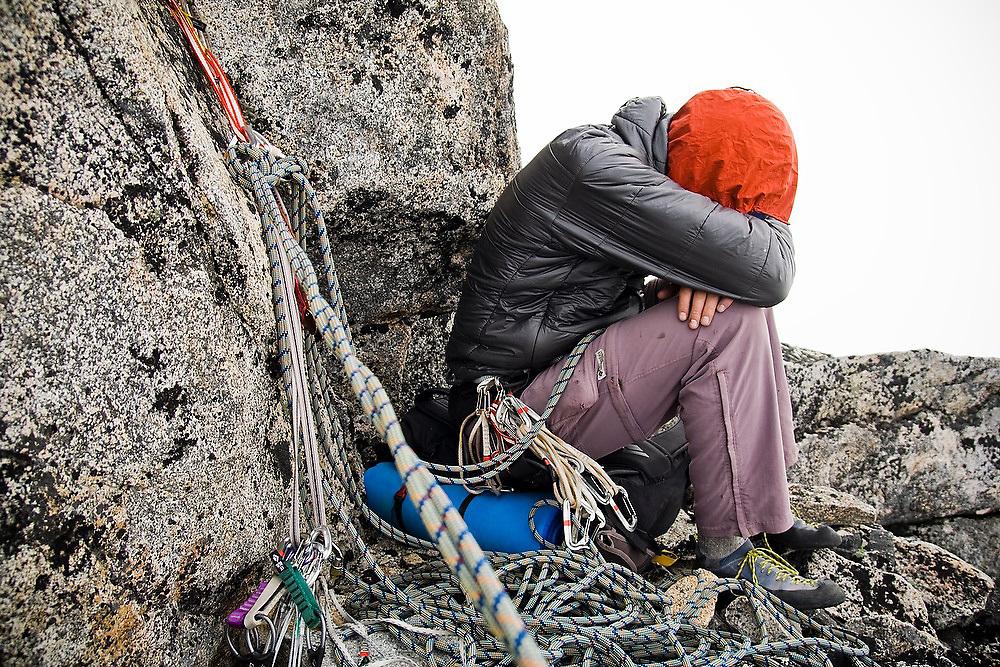 Climber Obadiah Reid curls up to stay warm at a belay station below the summit of Mount Stuart, Alpine Lakes Wilderness, Washington.