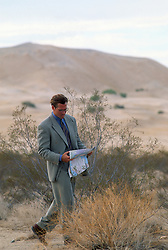 Man in a suit walking in the desert while reading a map