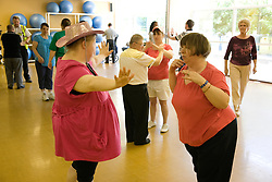 Group of Day Service users with learning disabilities dancing,