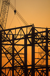 Stock photo of the silhouette of a man working at the top of the frame of a building under construction