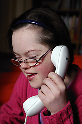 Teenage Downs Syndrome girl talking on the telephone,