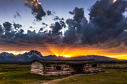 Light beams of the setting sun are parted by the jagged peaks of the peaks of the north Teton Range in Grand Teton Park.  The deserted homestead is the Cunningham Cabin built in 1885, Pierce Cunningham was one of the first settlers of Jackson Hole.