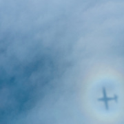 Shadow of the plane on clouds below, with a faint rainbow from the light on the clouds.