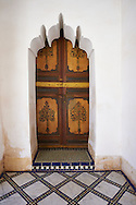 Berber Arabesque painted wood door and Zellige tile floor.The Petite Court, Bahia Palace, Marrakesh, Morroco .<br /> <br /> Visit our MOROCCO HISTORIC PLAXES PHOTO COLLECTIONS for more   photos  to download or buy as prints https://funkystock.photoshelter.com/gallery-collection/Morocco-Pictures-Photos-and-Images/C0000ds6t1_cvhPo<br /> .<br /> <br /> Visit our ISLAMIC HISTORICAL PLACES PHOTO COLLECTIONS for more photos to download or buy as wall art prints https://funkystock.photoshelter.com/gallery-collection/Islam-Islamic-Historic-Places-Architecture-Pictures-Images-of/C0000n7SGOHt9XWI