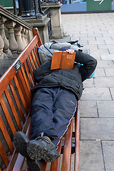 A Homeless man in Edinburgh relaxing on a public bench reading The Bible, Scotland, United Kingdom.