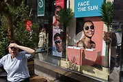A lady squints into the sun outside the window of the Sunglass Hut retailer in Covent Garden whose current slogan is 'Face the Sun', on 15th June 2019, in London, England.