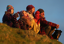 © London News Pictures. 20/01/2014. Glastonbury, UK. A family enjoy the warmth of the sun at Sunrise over Glastonbury Tor in Somerset on January 20, 2014.  Photo credit: Jason Bryant/LNP