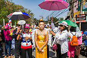 22 DECEMBER 2013 - BANGKOK, THAILAND: An anti-government protestor dressed as a Thai angel walks down the street in front of the home of caretaker Prime Minister Yingluck Shinawatra. Hundreds of thousands of Thais gathered in Bangkok Sunday in a series of protests against the caretaker government of Yingluck Shinawatra. The protests are a continuation of protests that started in early November and have caused the dissolution of the Pheu Thai led government of Yingluck Shinawatra. Protestors congregated at home of Yingluck and launched a series of motorcades that effectively gridlocked the city. Yingluck was not home when protestors picketed her home.     PHOTO BY JACK KURTZ
