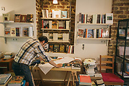 Rawad Saman, left, an employee at Pages bookshop, prepares the stock and displays a day before the official opening.