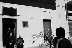 Reportage sviluppato ad Alessano (LE). Viene presa in considerazione fotograficamente, la gente che popola il paese nei suoi bar, piazze, strade, giardini pubblici. Ed, insieme a questa, i particolari e gli eventi caratterizzanti il luogo...La processione, nella mattinata della domenica delle Palme, percorre successivamente alla benedizione, le vie del centro storico e, dall'uscio di casa, alcuni fedeli osservano l'evento..