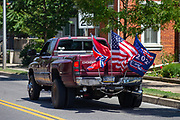 A pickup truck with a confederate flag, an American flag and a Trump 2020 flag drives on Chestnut Street during the Mifflinburg Pride Event.